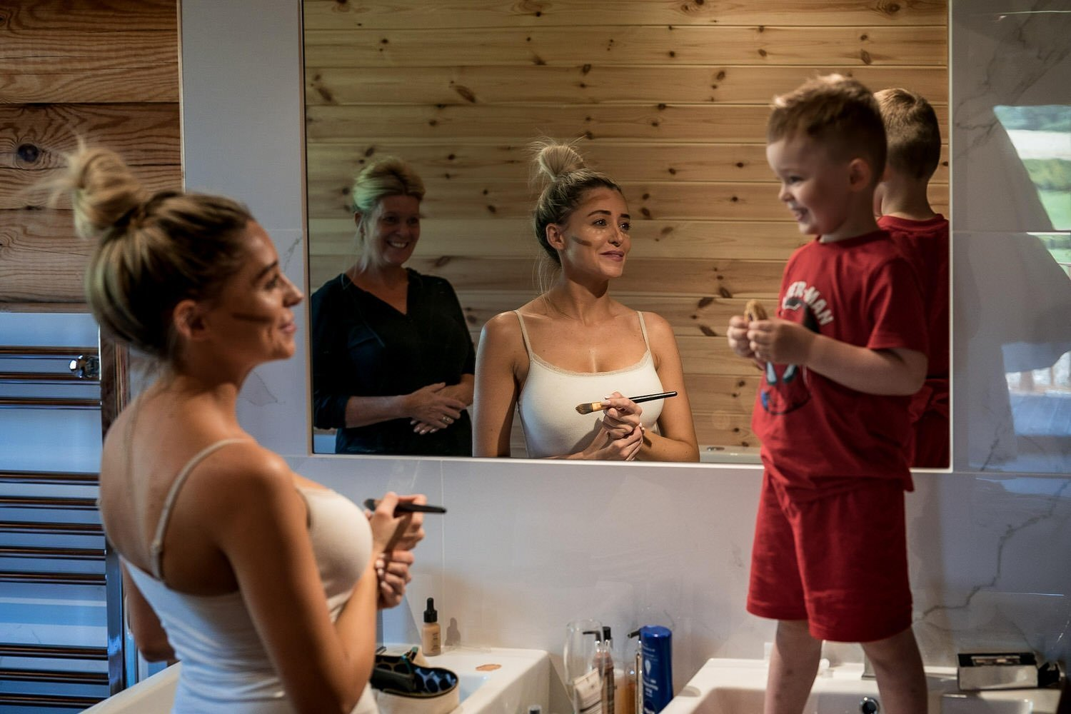 Foxton Lock Lodges Lockwood Weddings Photography Weddings Photography Bride doing her makeup while her son is standing in the sink looking at her