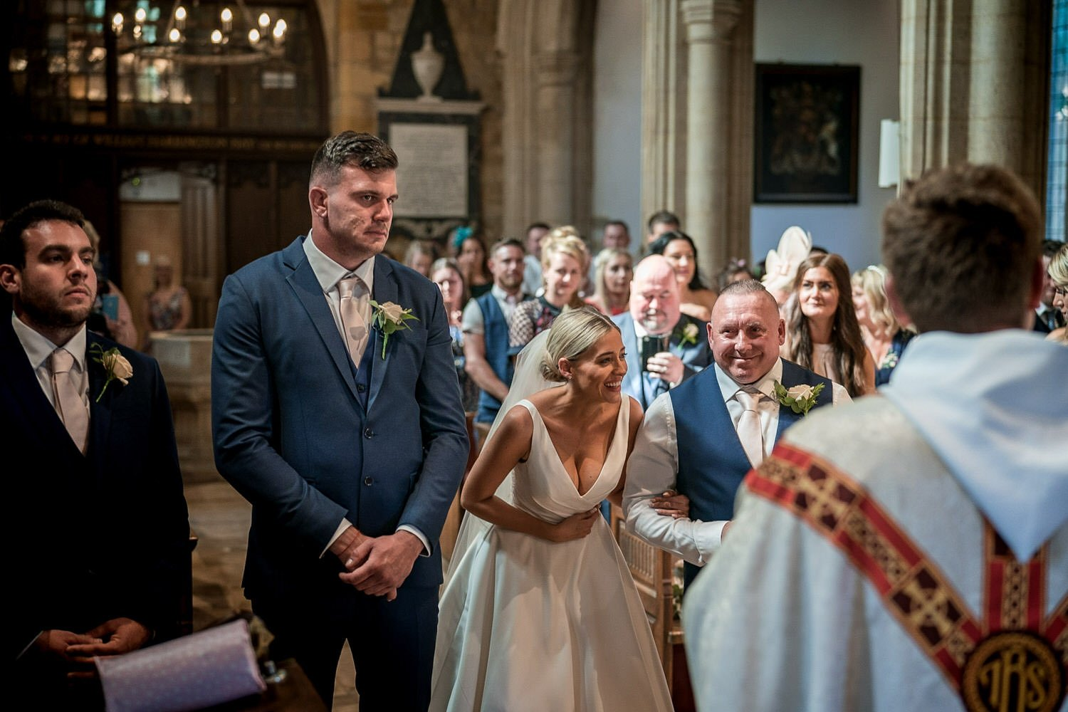 Great Bowden Parish Church Lockwood Weddings Photography Bride laughing at the vicar, groom looking serious