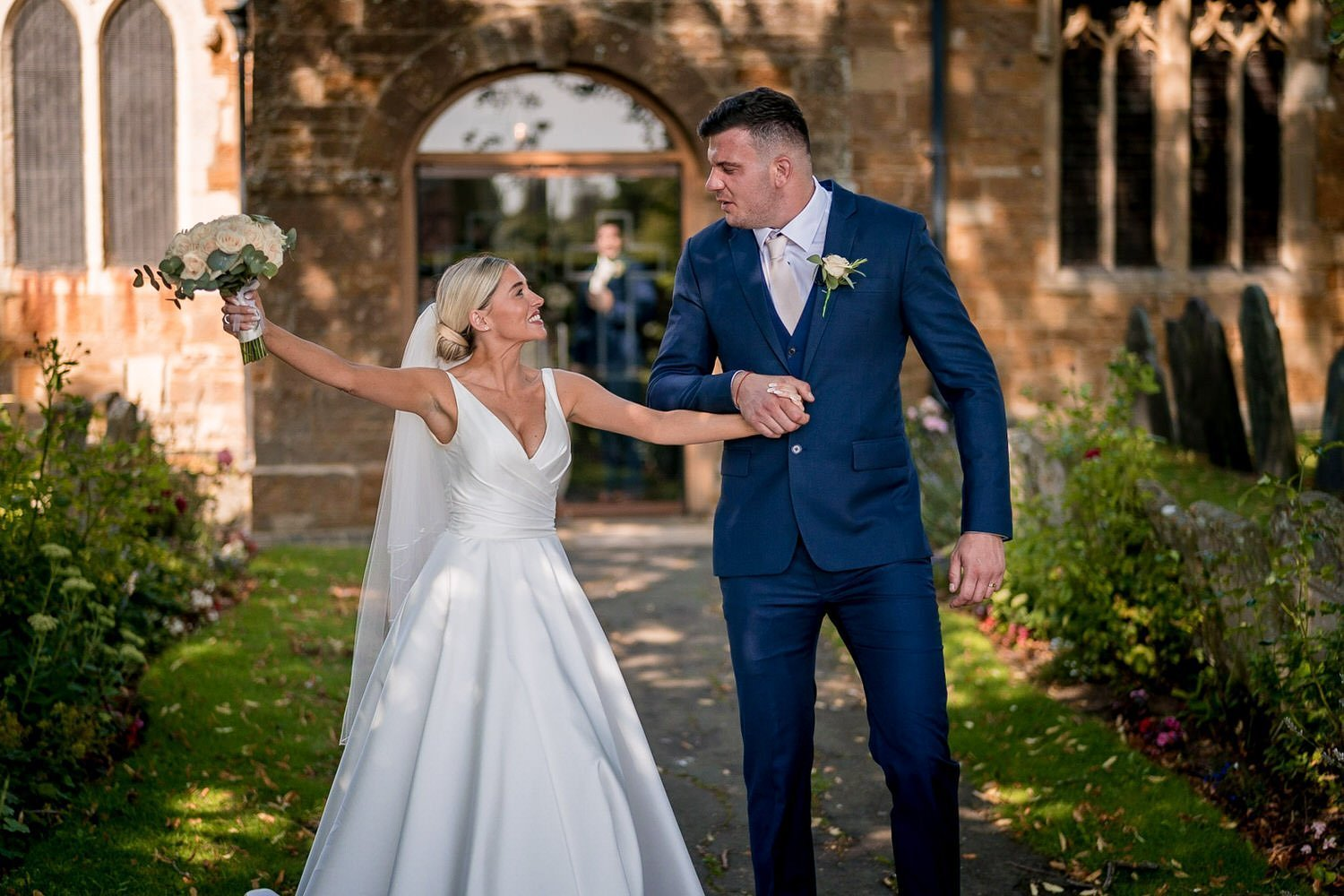 Great Bowden Parish Church Lockwood Weddings Photography bride and groom outside the church bride raising her bouquet in celebration and happiness