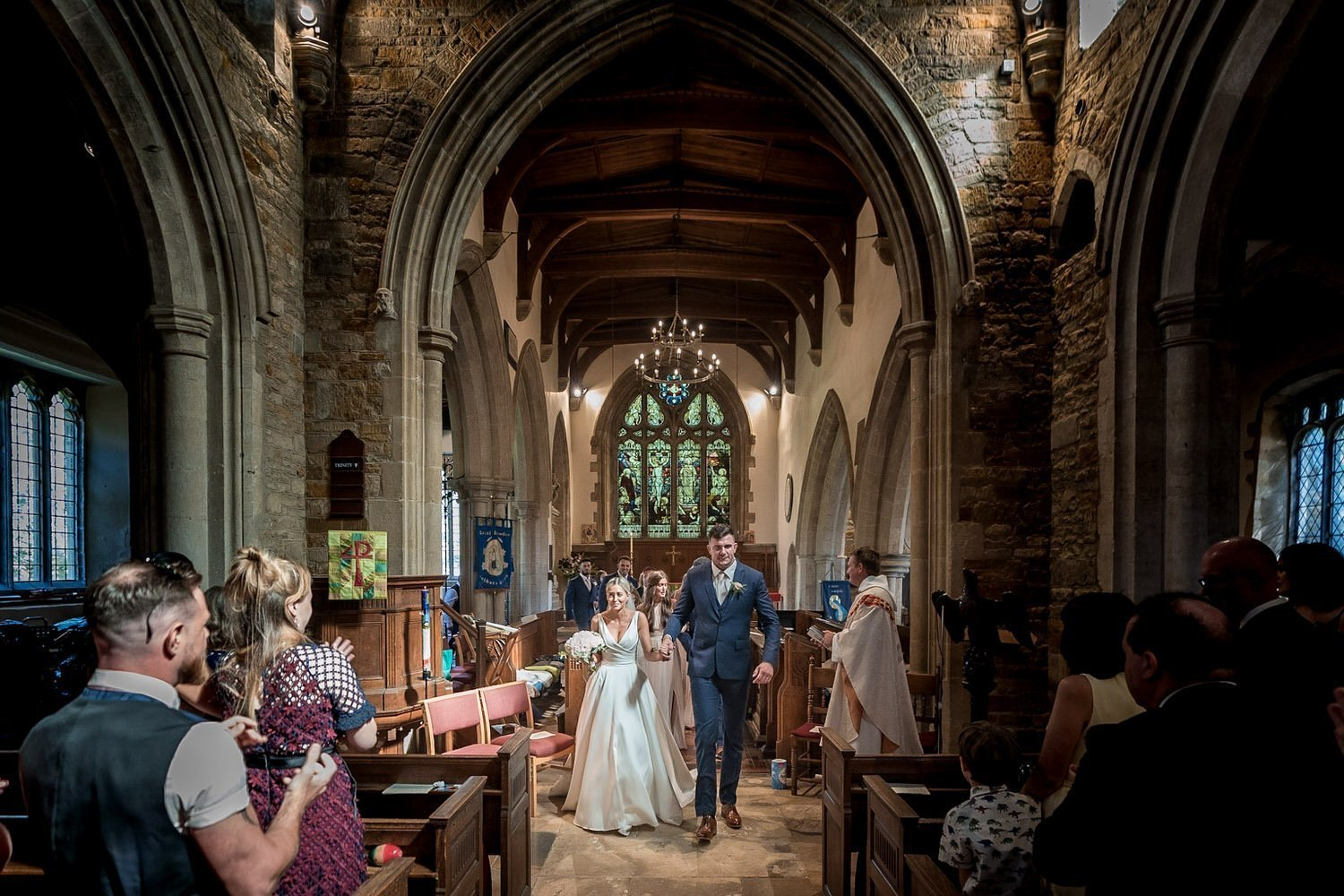 Great Bowden Parish Church Lockwood Weddings Photography bride and groom walking down the aisle as man husband and wife wide view stained glass