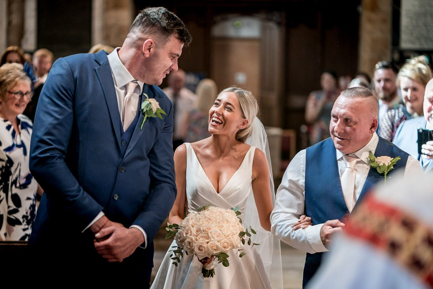 Great Bowden Parish Church Lockwood Weddings Photography bride arrives at the foot of the aisle and sees her groom husband for the first time, broad smiles and laughter father proud