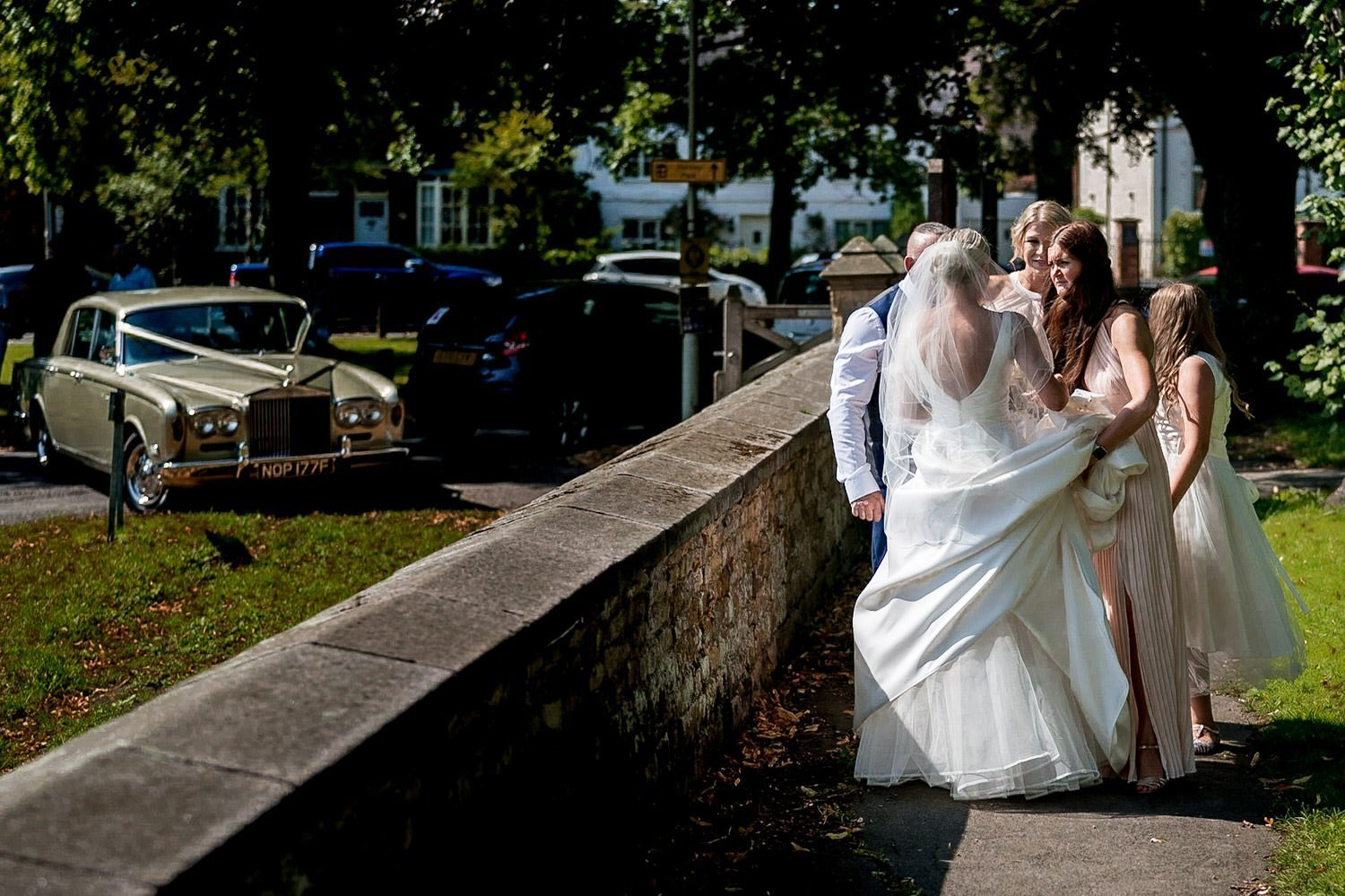Great Bowden Parish Church Lockwood Weddings Photography bride huddled with her bridesmaids outside the church before the ceremony wedding car in the background