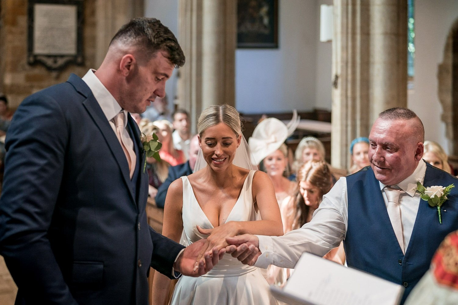 Great Bowden Parish Church Lockwood Weddings Photography father of the bride hanging his daughter hand to her husband smiles everywhere