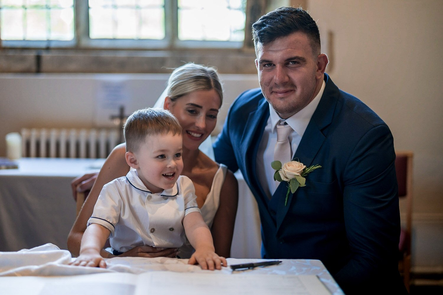 Great Bowden Parish Church Lockwood Weddings Photography groom bride and their son at the wedding signing register