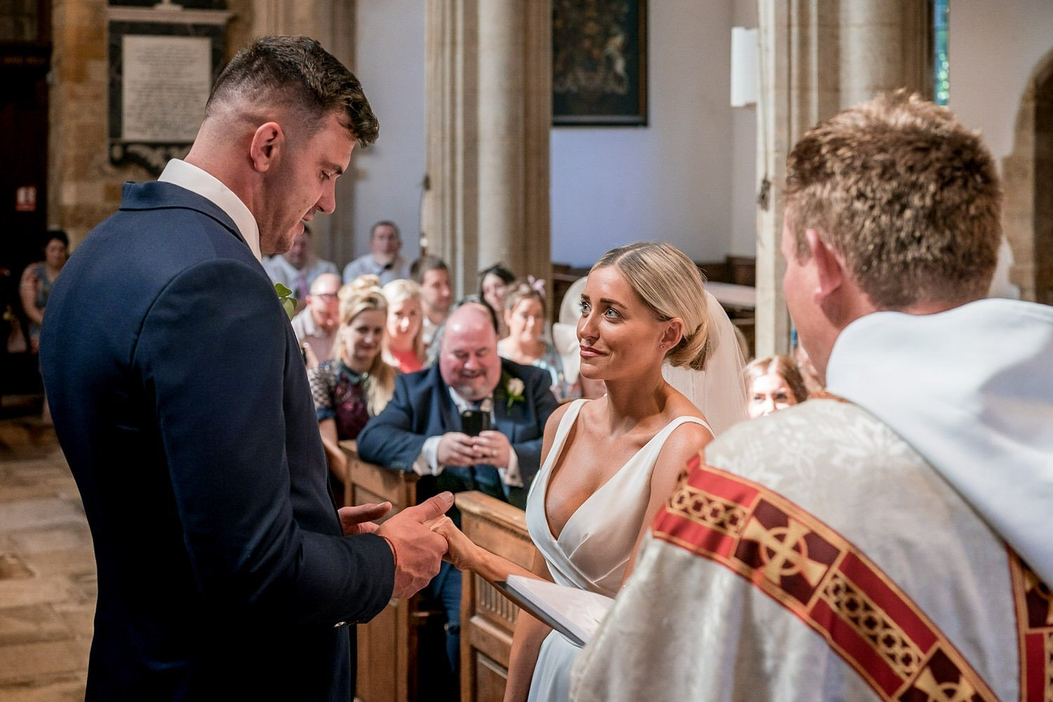 Great Bowden Parish Church Lockwood Weddings Photography groom holding his brides hands as they take their marriage vows