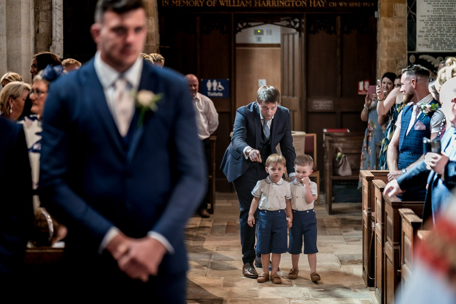 Great Bowden Parish Church Lockwood Weddings Photography groom looking at the floor nervously as the page boys are pointed down the aisle to their seats