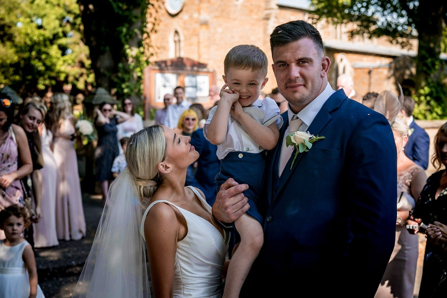 Great Bowden Parish Church Lockwood Weddings Photography groom outside the church holding up their son with him beaming with smiles bride looking up at her son