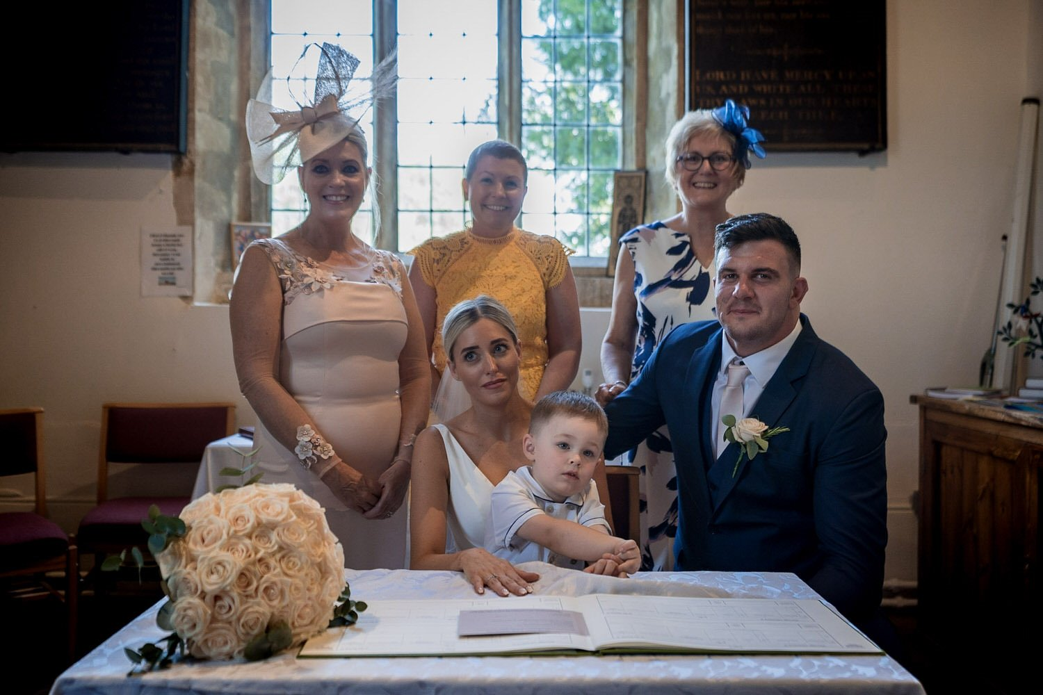 Great Bowden Parish Church Lockwood Weddings Photography group photos in the church at the wedding signing register