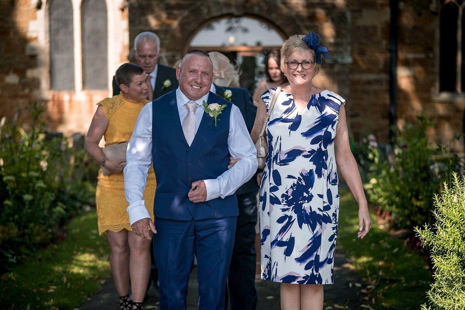 Great Bowden Parish Church Lockwood Weddings Photography guest photos as they leave the church father of the bride
