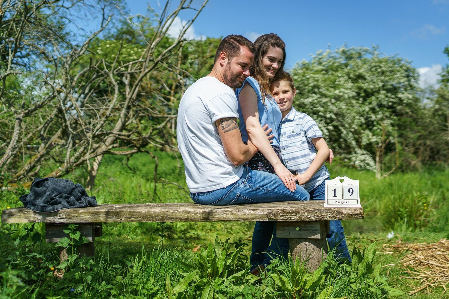 Stoke Bruerne Northamptonshire Engagement Family Photography couple and their son sat on a bench having a cuddle in the nature reserve