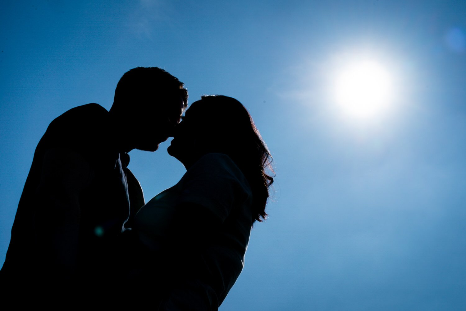 Stoke Bruerne Northamptonshire Engagement Family Photography couple kissing under the sun and perfect blue sky