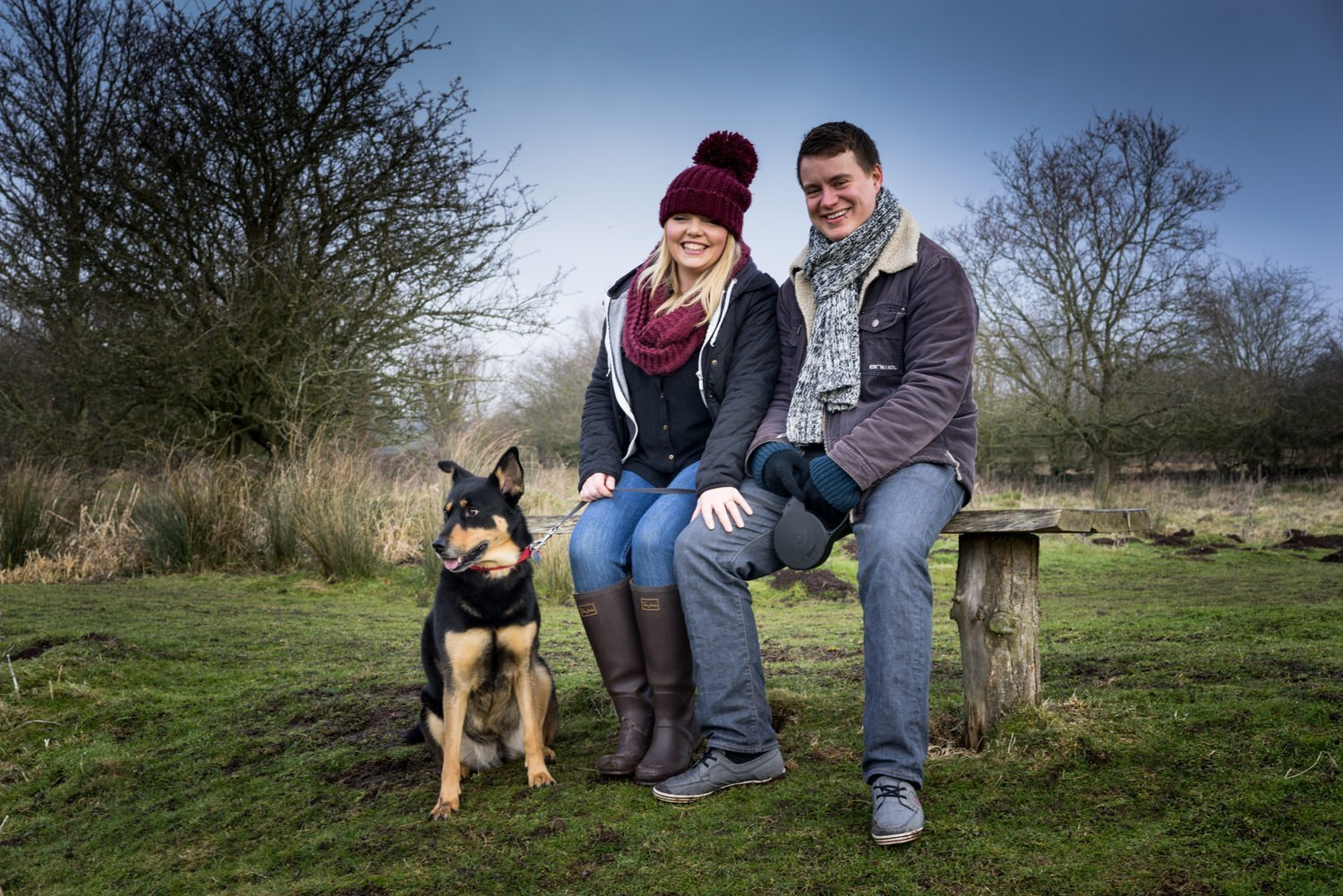 Stoke Bruerne Northamptonshire Engagement Family Photography couple sat on the bench in the nature reserve while their dog looks on