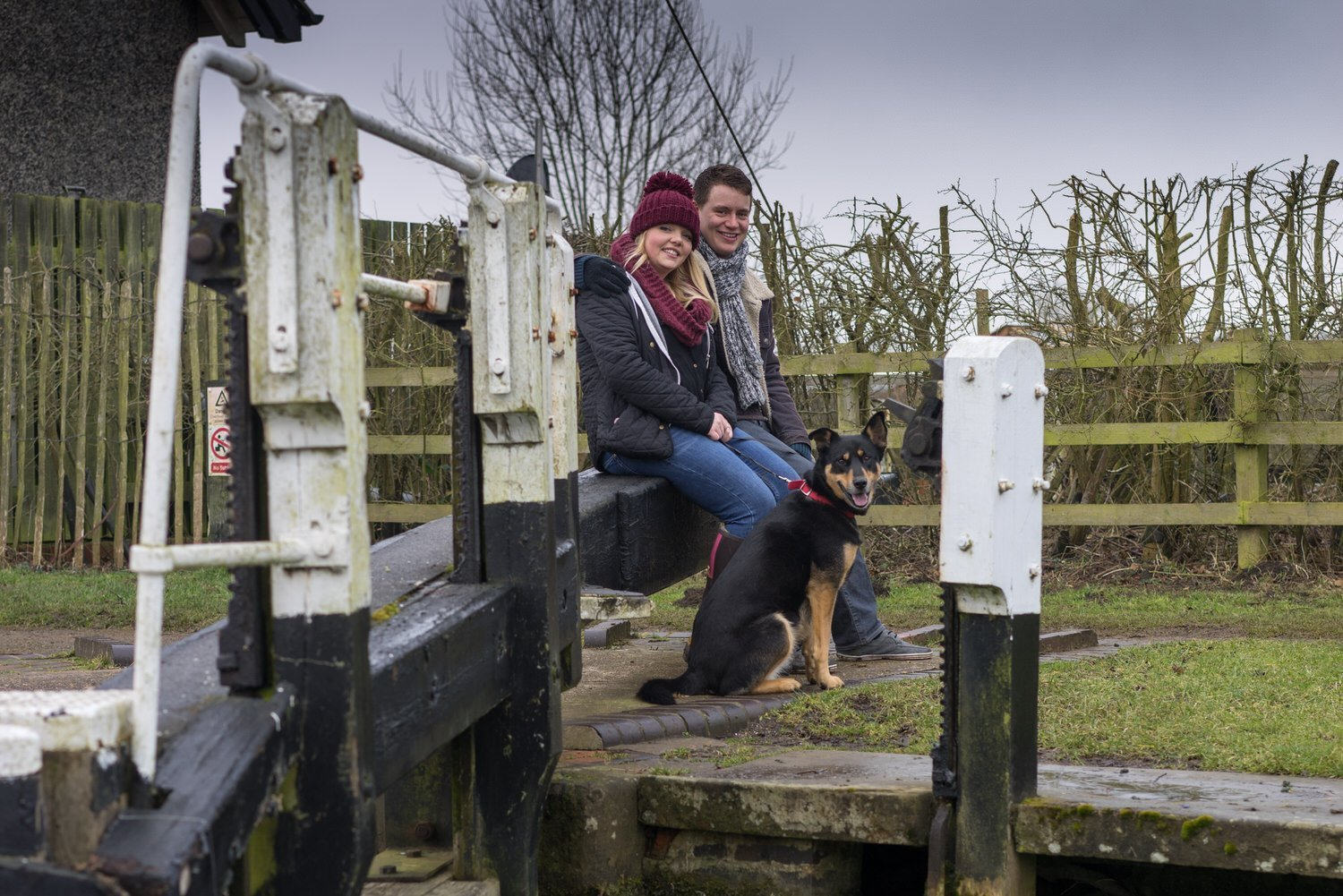 Stoke Bruerne Northamptonshire Engagement Family Photography couple sat on the lock gate with their puppy looking happy