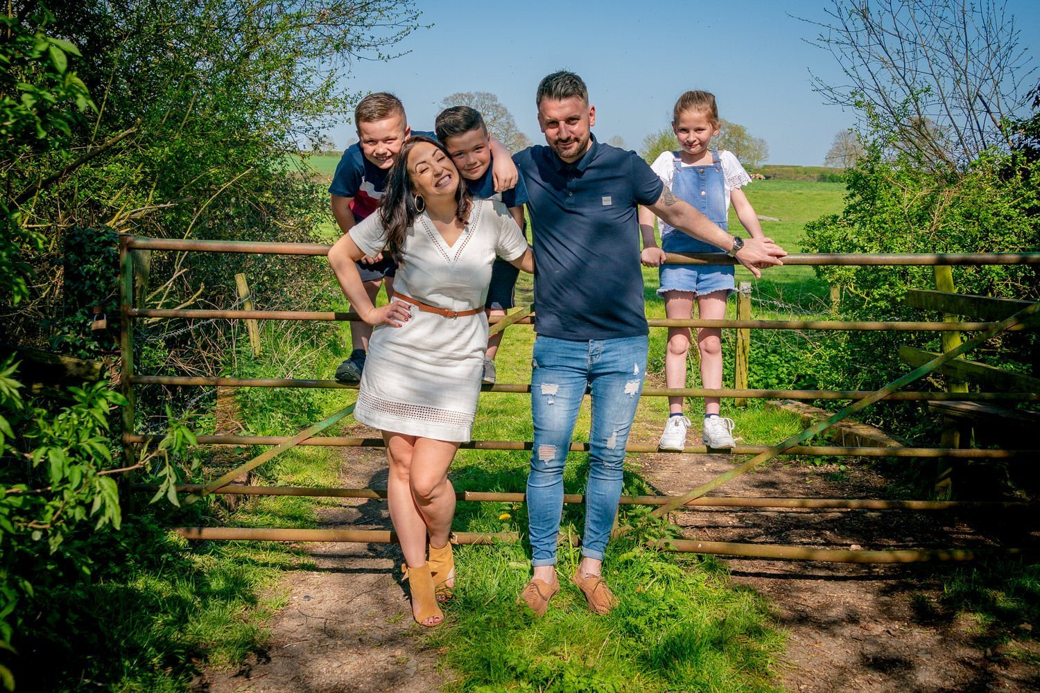 Stoke Bruerne Northamptonshire Engagement Family Photography couple standing in front of the gate as their children sit on it boy being silly and tickling his mum mother