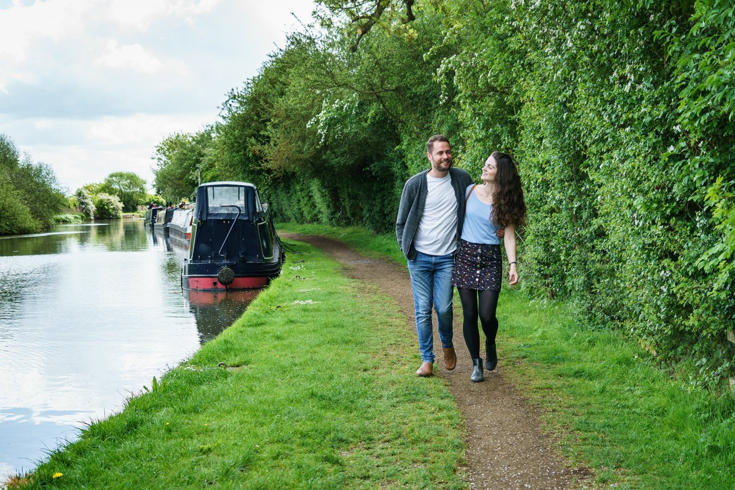 Stoke Bruerne Northamptonshire Engagement Family Photography couple walking along the tow path arms around each other looking loved up