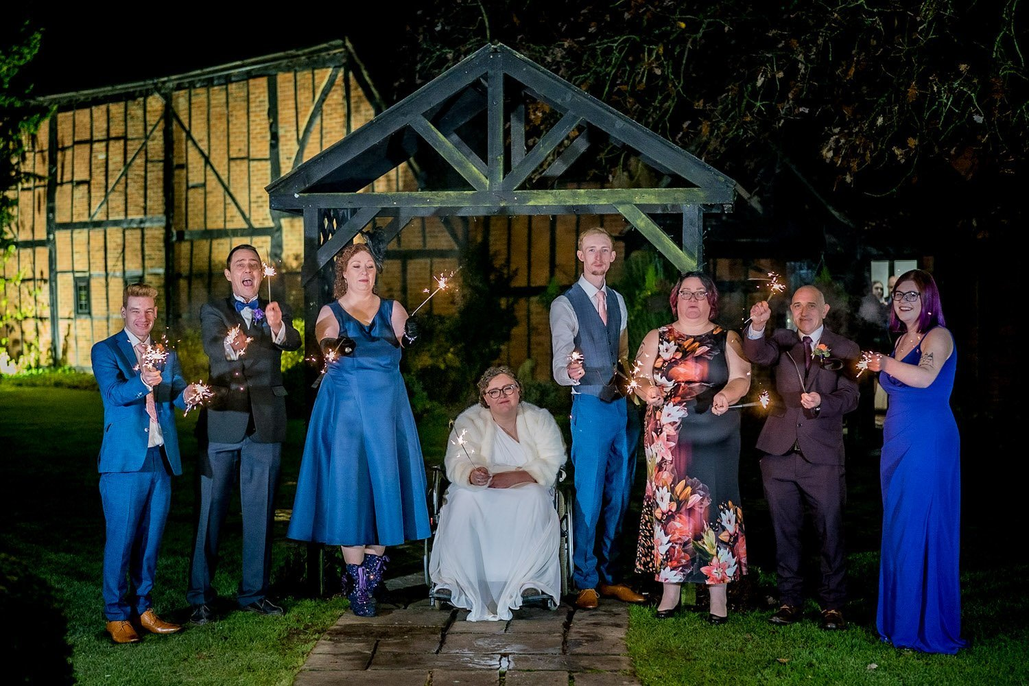 The Barns Hotel Bedford Wooten Weddings Photography Bridal party playing with sparklers outside the barn under the wooden archway