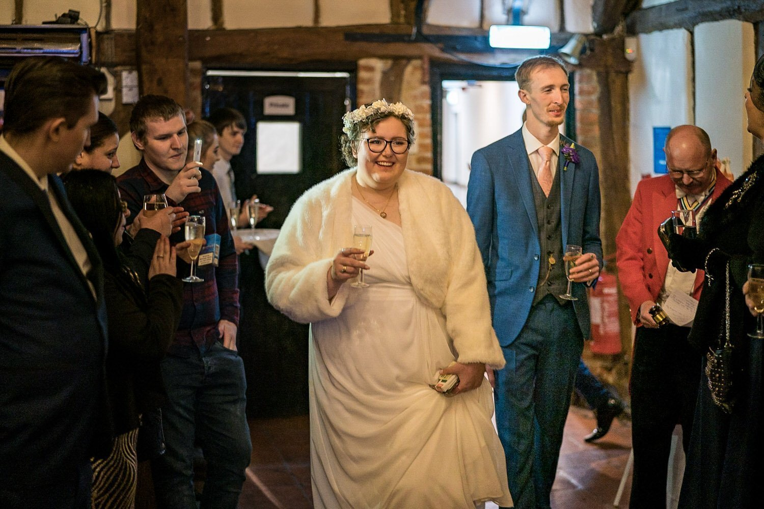 The Barns Hotel Bedford Wooten Weddings Photography Bride and groom arriving to their evening ceremony with glasses of champagne in hand