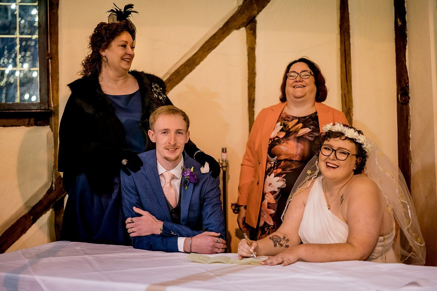 The Barns Hotel Bedford Wooten Weddings Photography Bride and groom signing the wedding register with their mums behind