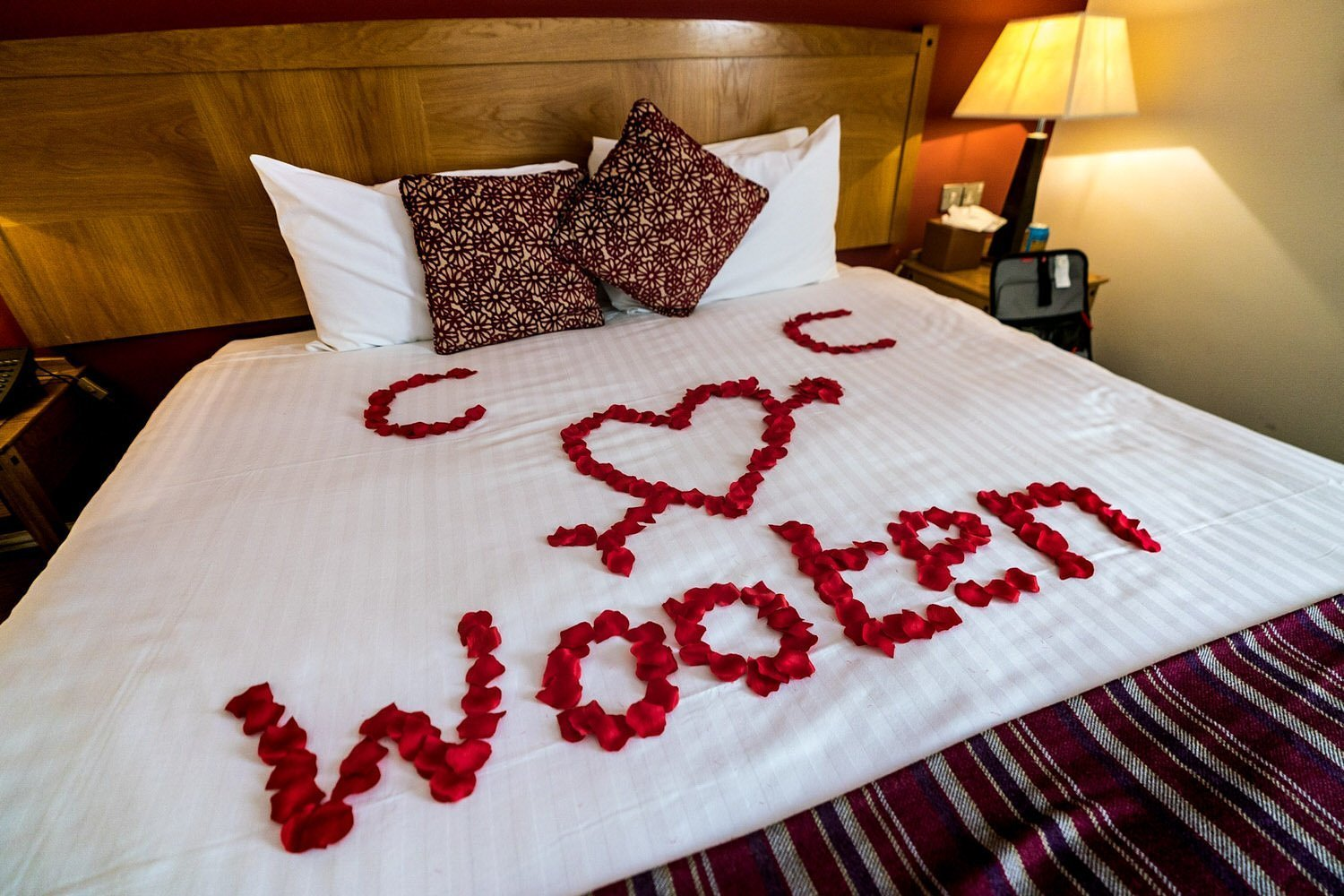 The Barns Hotel Bedford Wooten Weddings Photography Red rose petals on the bed in the bridal suite from the hotel staff
