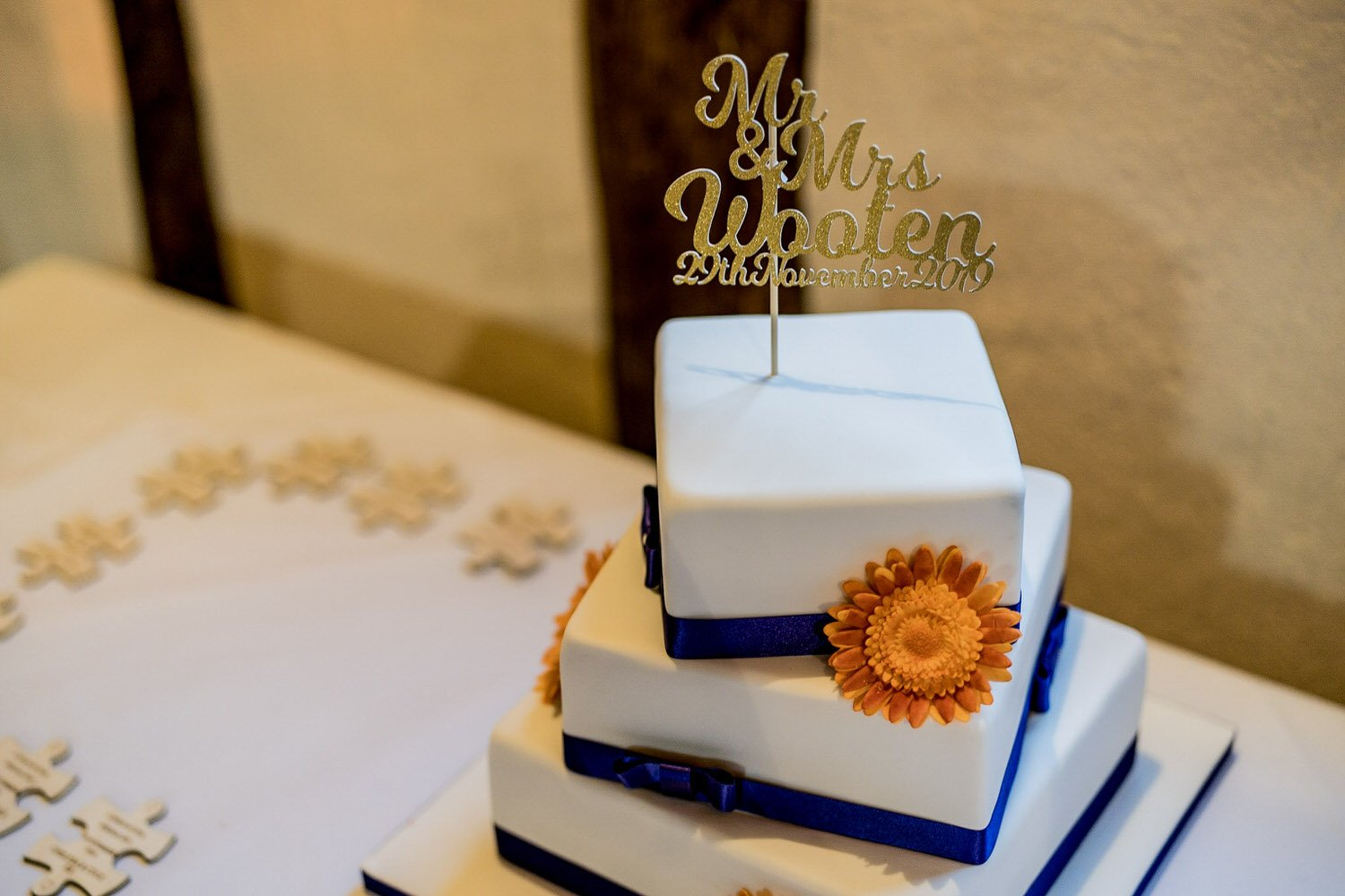 The Barns Hotel Bedford Wooten Weddings Photography Wedding cake with the couples name in gold sparkles