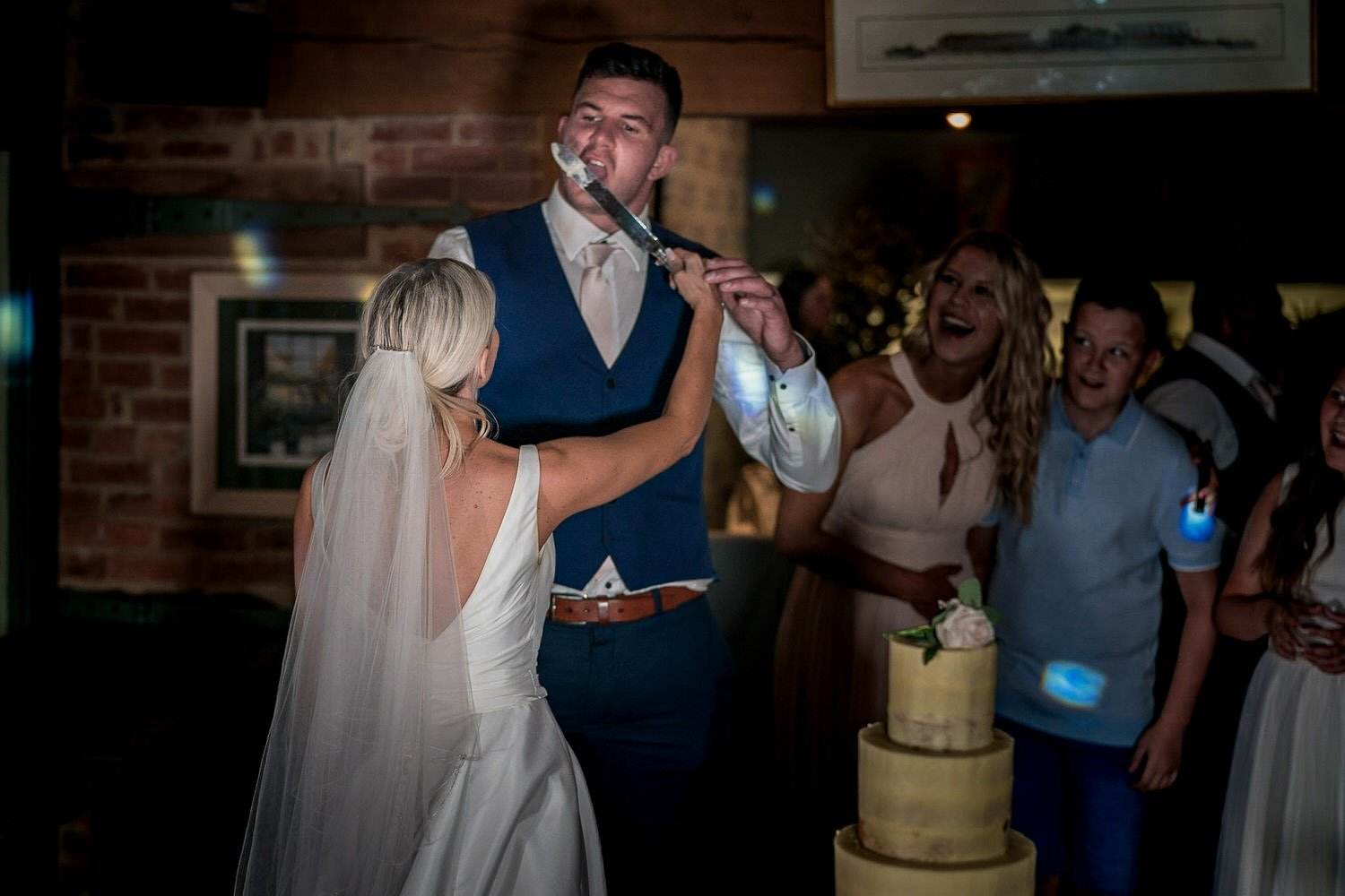 The Waterfront Market Harborough Lockwood Weddings Photography groom licking the cake icing off the knife bride holding the knife up