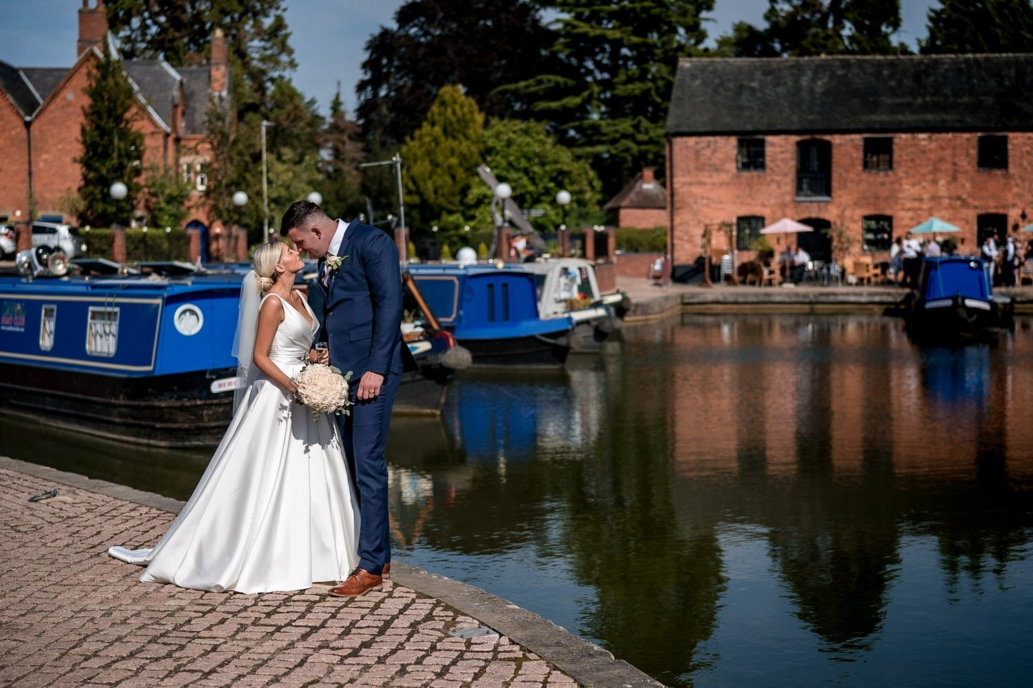 The Waterfront Market Harborough Weddings Photography Bride and Groom on the tow path in front of the barges with the venue in the background