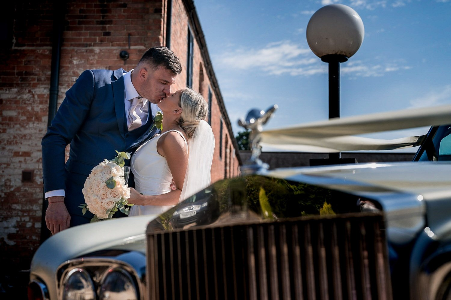 The Waterfront Market Harborough Weddings Photography Groom kissing his bride on the tow path rolls royce