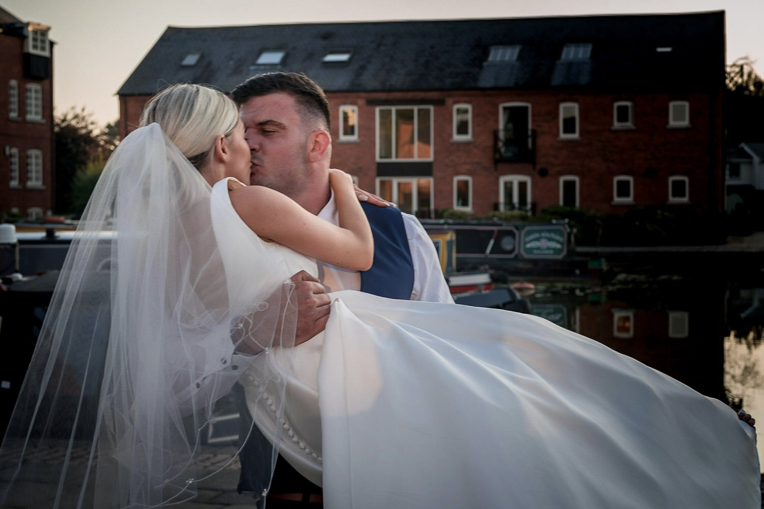 The Waterfront Market Harborough Weddings Photography Groom kissing his bride on the tow path holding her in his arms barges in the background
