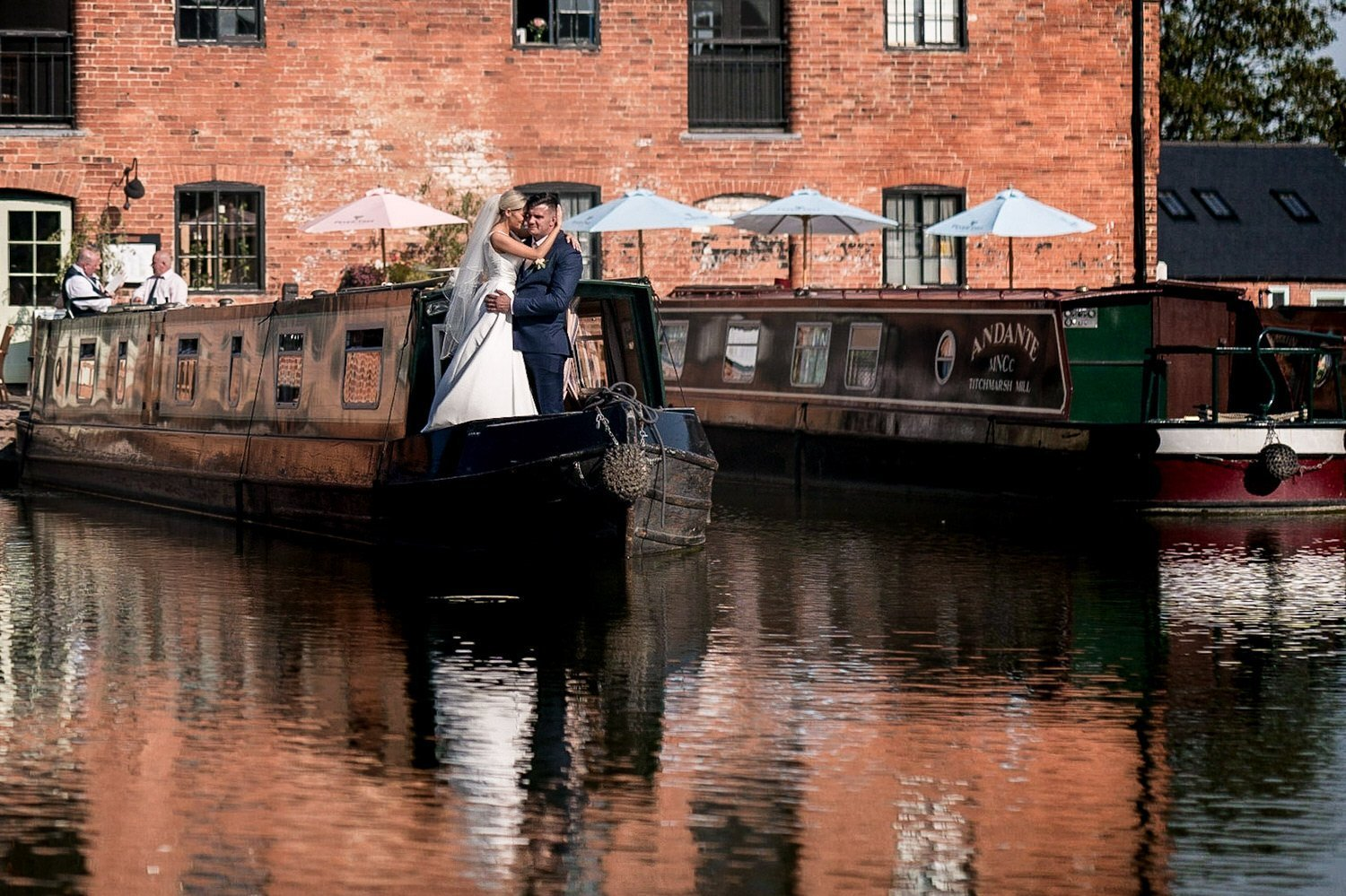 The Waterfront Market Harborough Weddings Photography bride and groom embracing on the front step of a canal barge with the venue behind them