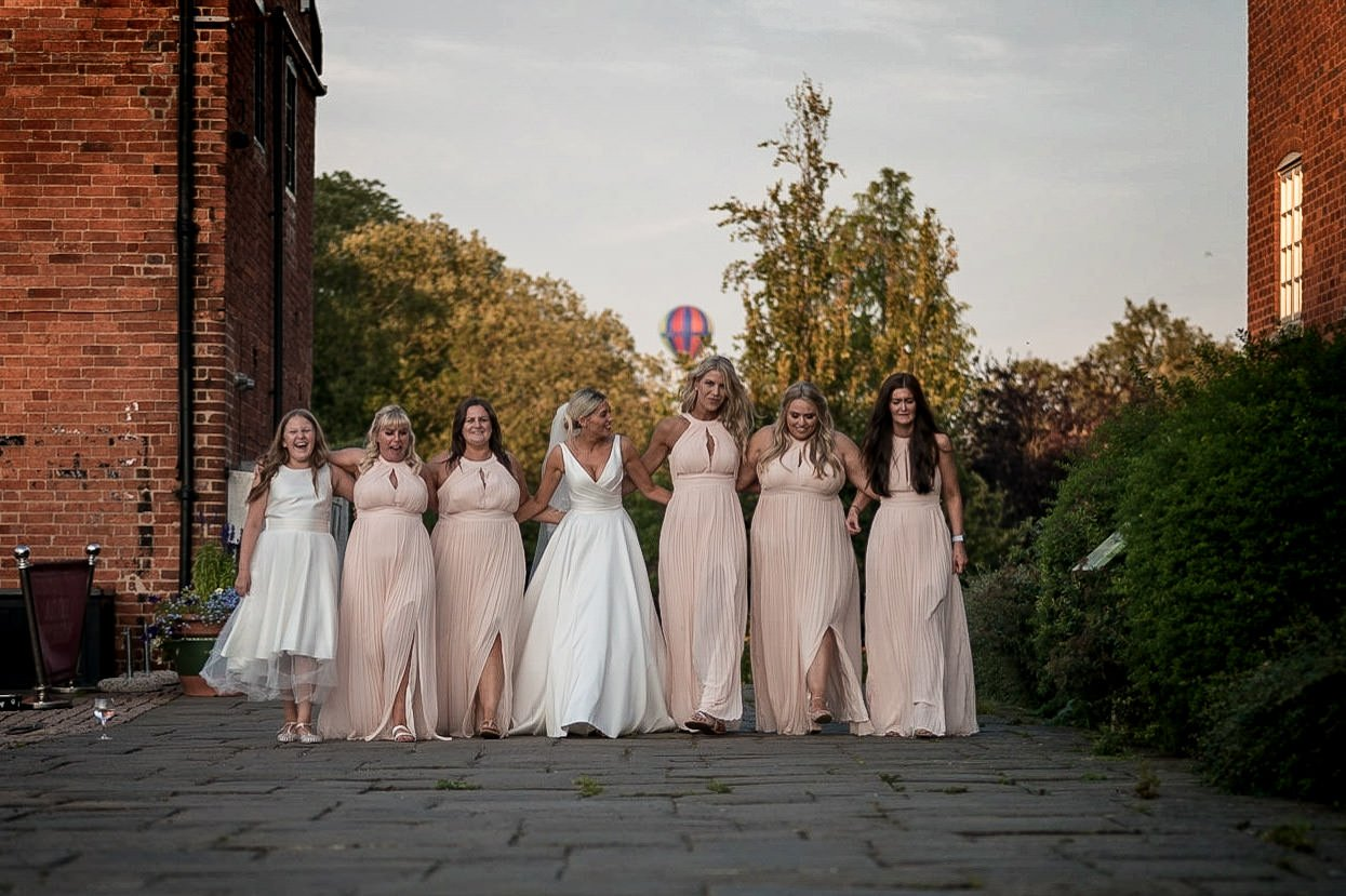 The Waterfront Market Harborough Weddings Photography bride walking along the tow path with her bridesmaids arm in arm hot air balloon rising behind them