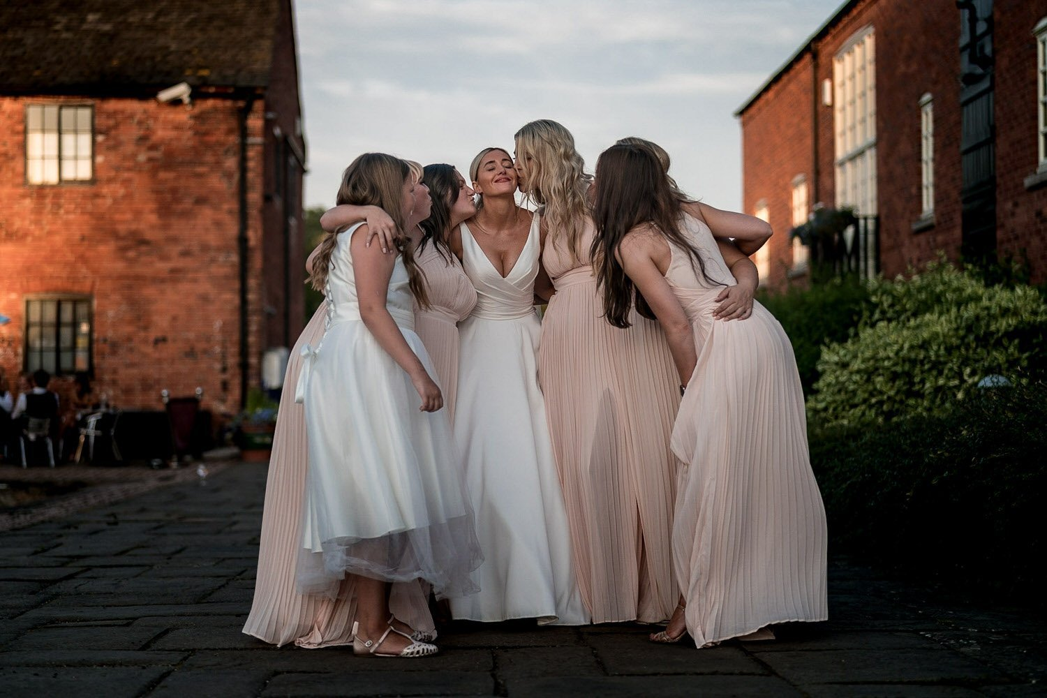 The Waterfront Market Harborough Weddings Photography bridesmaids hugging the bride on the tow path outside the venue