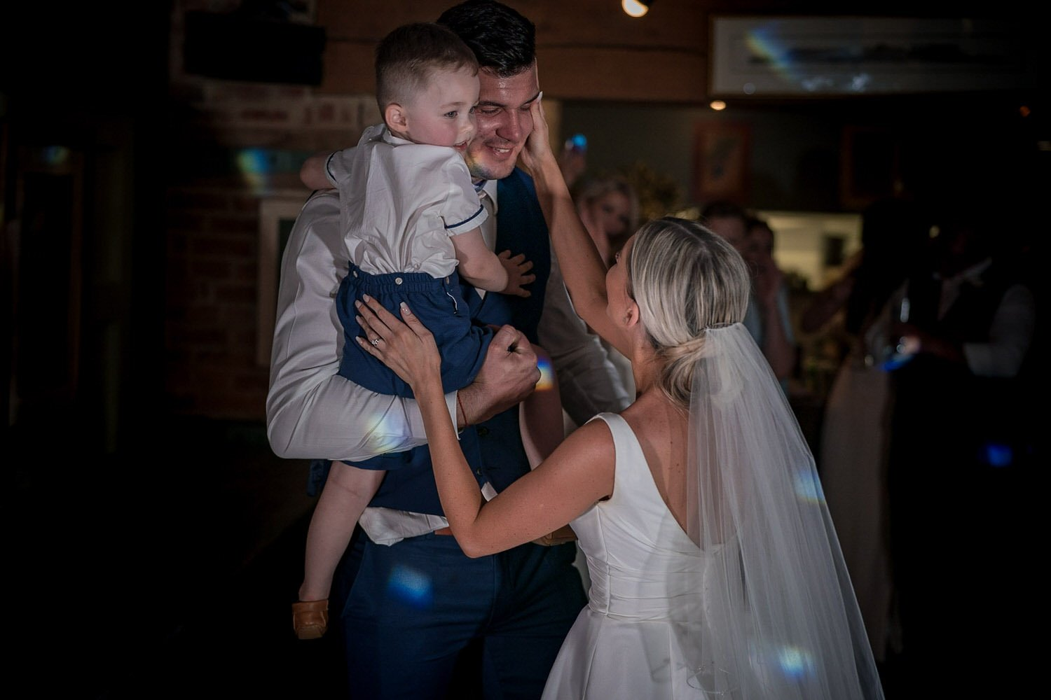 The Waterfront Market Harborough Weddings Photography groom holding his son high in his arms while his wife bride wipes away a tear