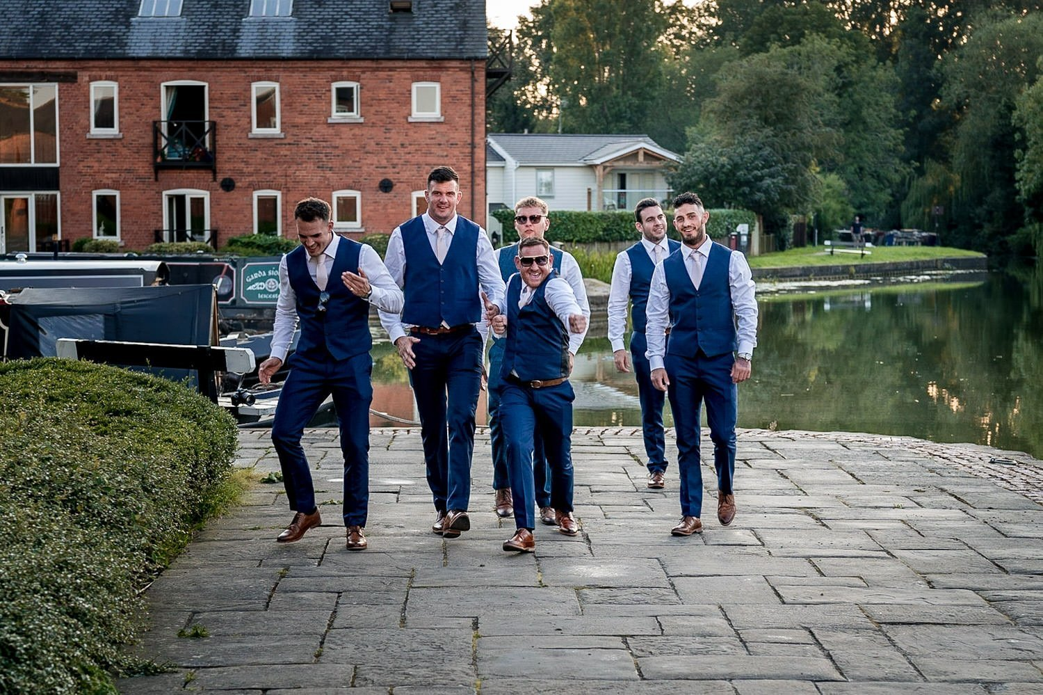 The Waterfront Market Harborough Weddings Photography groom walking along the tow path with his ushers doing stupid dancing silly walks
